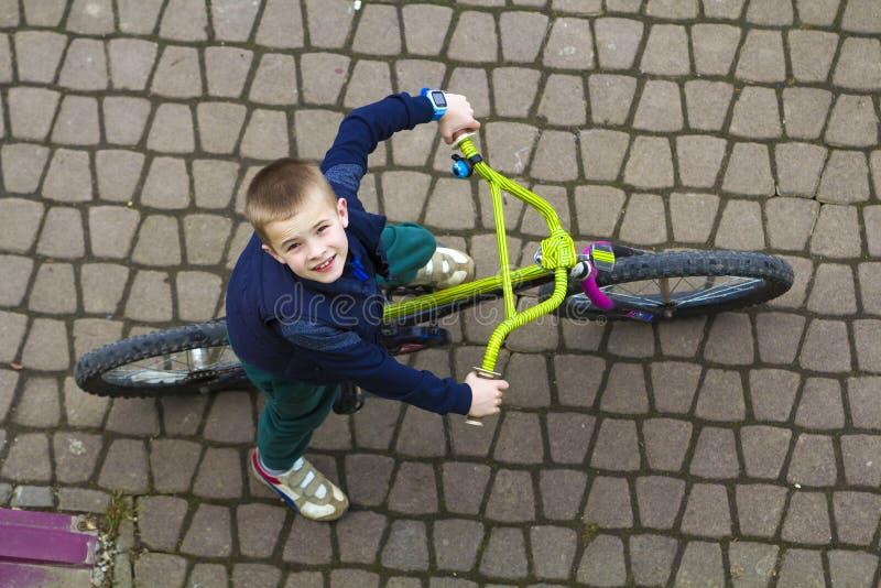 Bästa sikt av den stiliga unga le pojken som rider en cykel på den kalla vårdagen som uppåt ser Utomhus aktiviteter sund livsstil royaltyfri foto
