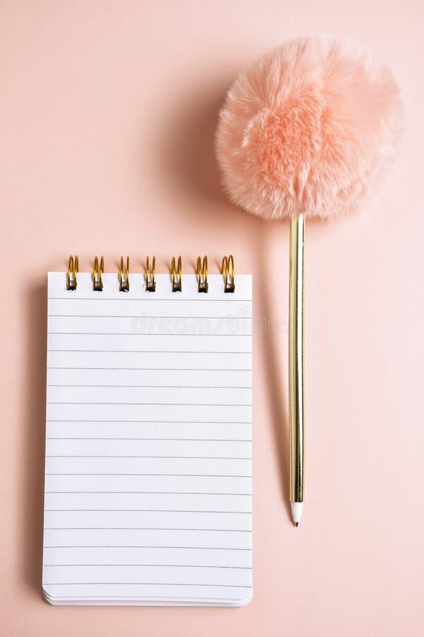 Bästa sikt av den tomma anteckningsboken med den roliga fluffiga pennan på rosa pastellfärgad bakgrund med kopieringsutrymme, ver royaltyfri bild