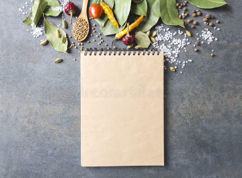 Bästa sikt av den tomma kokboken och lott av spieces och örter på det gråa köksbordet T?m utrymme f?r din text och planl?gg arkivfoton