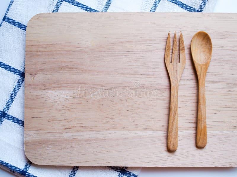 Bästa sikt av den träbestick, skeden och gaffeln på skärbräda royaltyfria foton