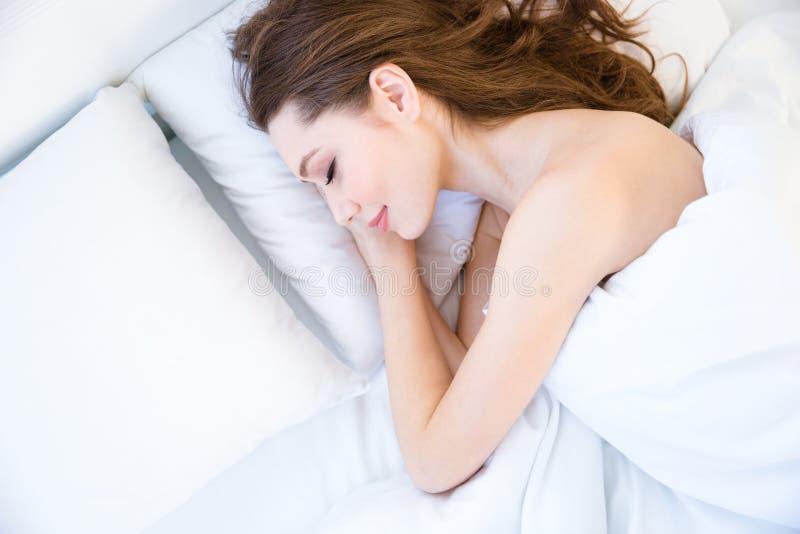 Bästa sikt av den trötta härliga unga kvinnan som sover på säng royaltyfria foton