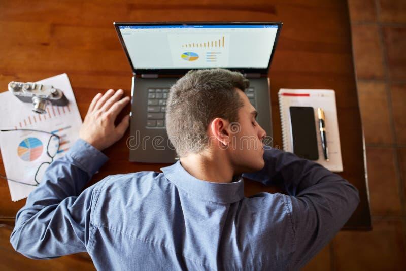 Bästa sikt av den trötta utmattade affärsmannen som sover på bärbar datortangentbordet på arbetsplatsen Stilig överansträngd free arkivfoto