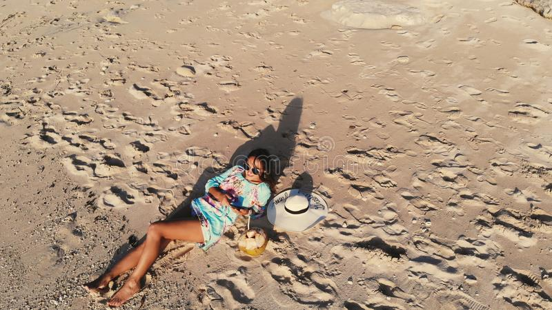 Bästa sikt av den unga brunettkvinnan i solglasögon som ligger på den tropiska paradisstranden och bruksmobiltelefonen under härl royaltyfri foto