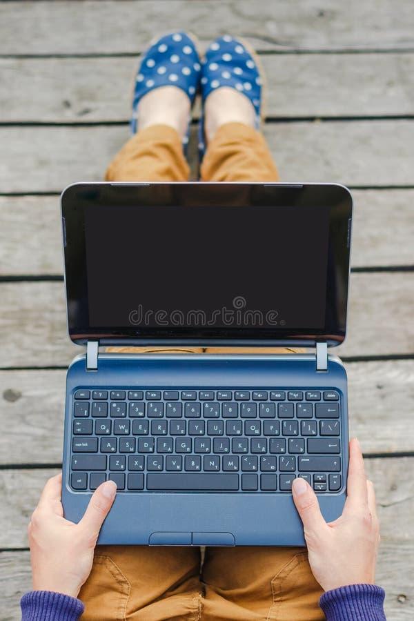 Bästa sikt av den unga hipsterflickan som använder bärbara datorn royaltyfria foton