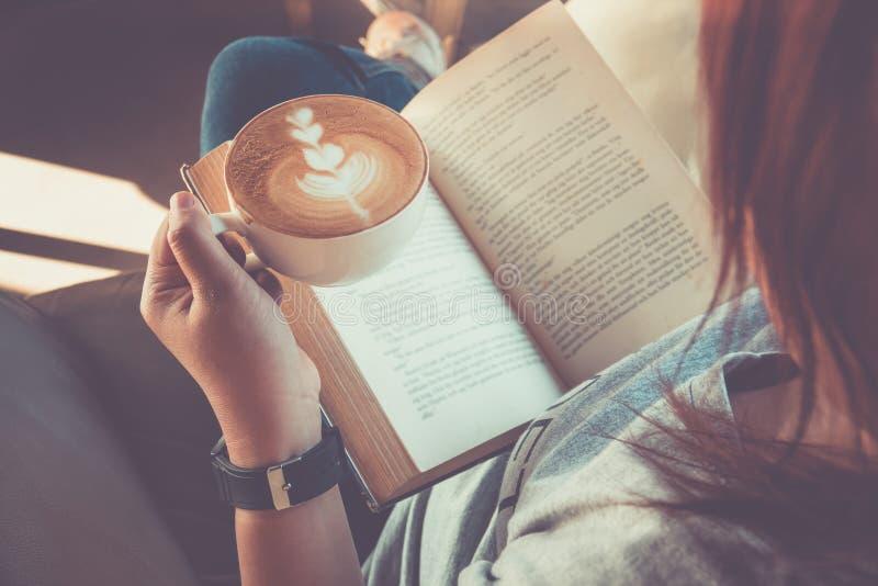 Bästa sikt av den unga kvinnan som läser en bok- och innehavkopp kaffe royaltyfri foto