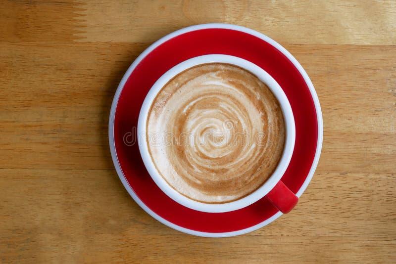 Bästa sikt av den varma koppen för kaffecappuccinolatte på röd keramisk sås fotografering för bildbyråer