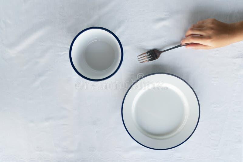 Bästa sikt av den vita blåa maträtten för matmatställe på tygborddukbakgrund arkivbild