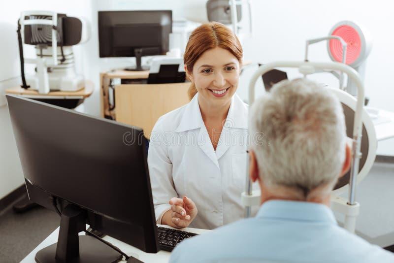 Bästa sikt av den yrkesmässiga ögonspecialisten som talar till patienten royaltyfria bilder
