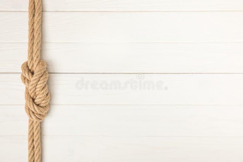 bästa sikt av det bruna nautiska repet med fnuren på vit träyttersida arkivfoto