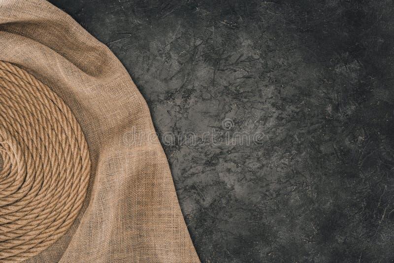 bästa sikt av det bruna nautiska repet som är ordnat i cirkel på säckväv på mörker arkivbilder
