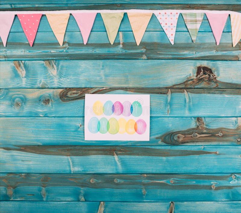 bästa sikt av det färgrika lyckliga easter hälsningkortet på blått arkivfoto