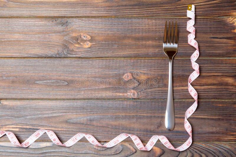 Bästa sikt av det krullade fetmabegreppet med gaffeln och mäta bandet på träbakgrund med utrymme för dina idérika idéer arkivbilder