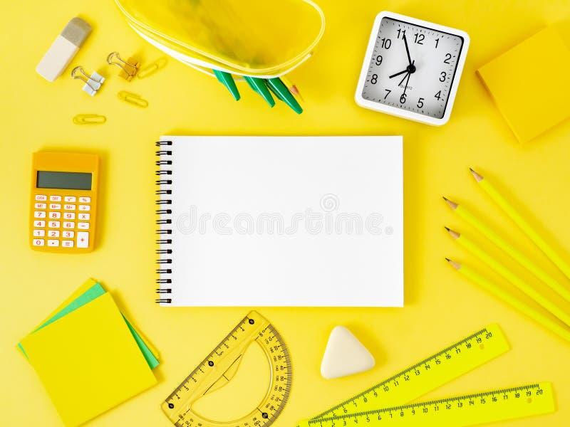 Bästa sikt av det ljusa gula kontorsskrivbordet med den tomma notepaden, sch royaltyfri bild