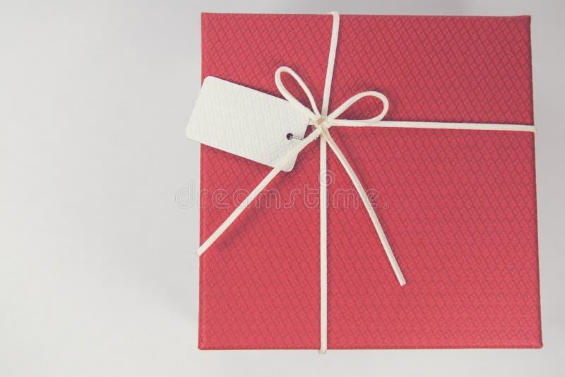 Bästa sikt av det röda bandet för whit för gåvaask på vit bakgrund Utrymme för produktplacering royaltyfria foton