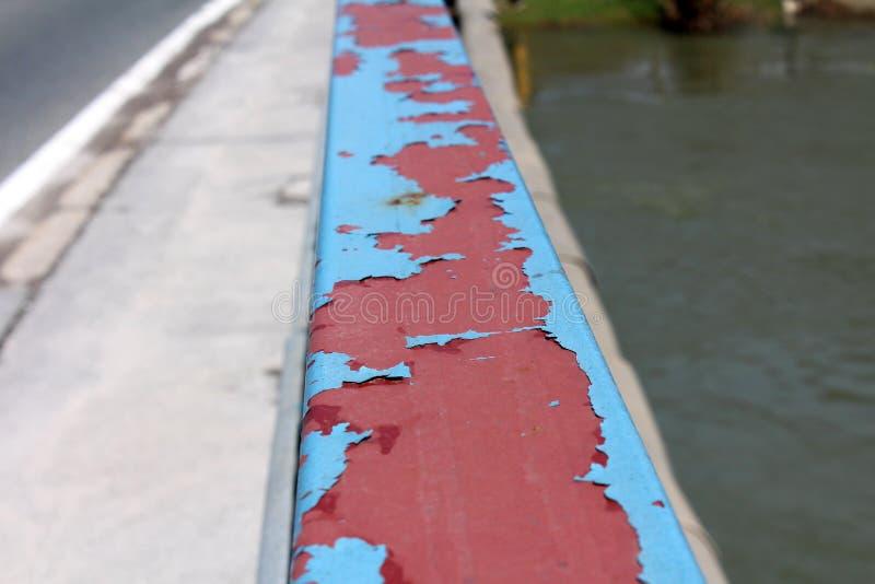 Bästa sikt av det starka metallstaketet med sprucken blå målarfärg på den lokala bron som omges med vägen på en sida och floden p arkivbild