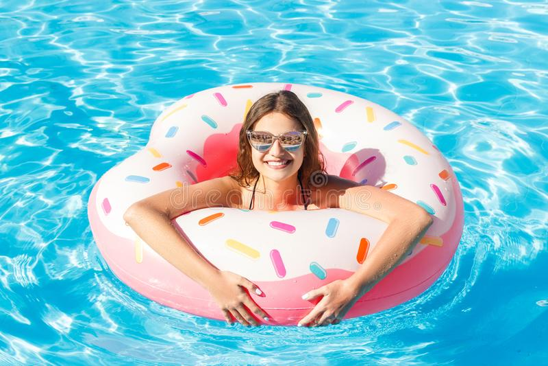 Bästa sikt av det unga kvinnliga badet med rosa färgcirkeln i pöl royaltyfria bilder