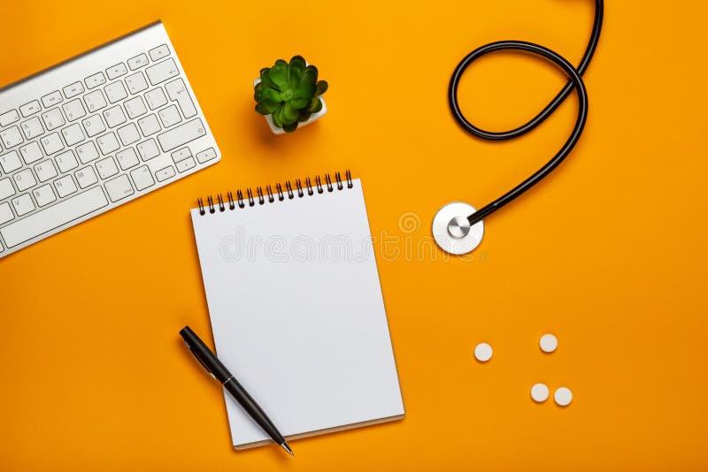 Bästa sikt av doktors skrivbord med stetoskoptangentbordnotepaden och penna, recept och piller royaltyfria bilder