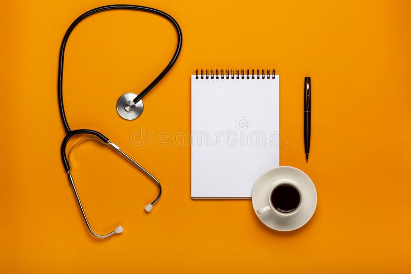 Bästa sikt av doktorsskrivbordtabellen med stetoskopet, kaffe och tomt papper på skrivplattan med pennan Bästa sikt med kopiering royaltyfria bilder
