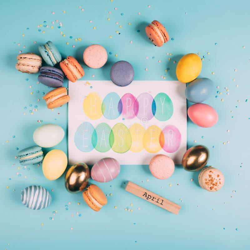 bästa sikt av easter ägg och macarons runt om lyckligt easter hälsningkort arkivbild