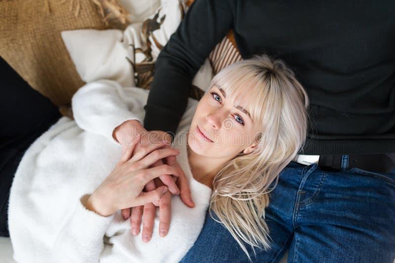 Bästa sikt av en gullig blond kvinna som hemma ligger på hennes pojkvänvarv på en soffa arkivbild