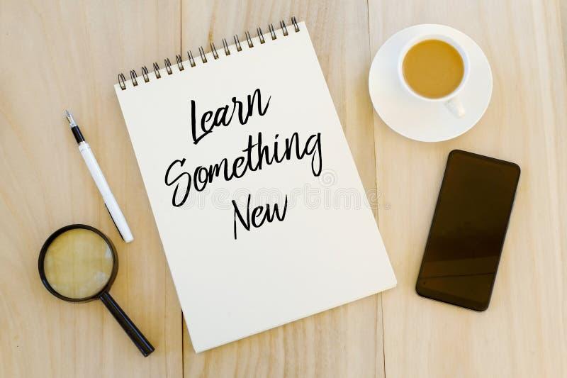 Bästa sikt av en kopp kaffe, en mobiltelefon, en penna och en anteckningsbok som är skriftliga med att lära något som är ny på tr royaltyfri foto