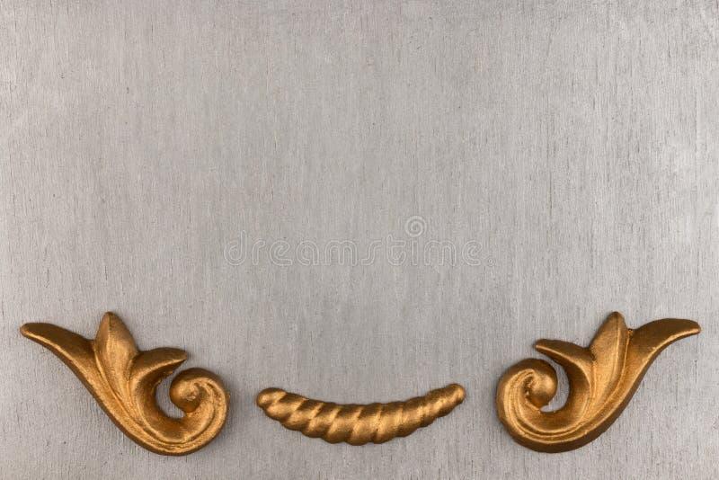 Bästa sikt av en lyxig guld- stuckatur på en silverbakgrund arkivfoton