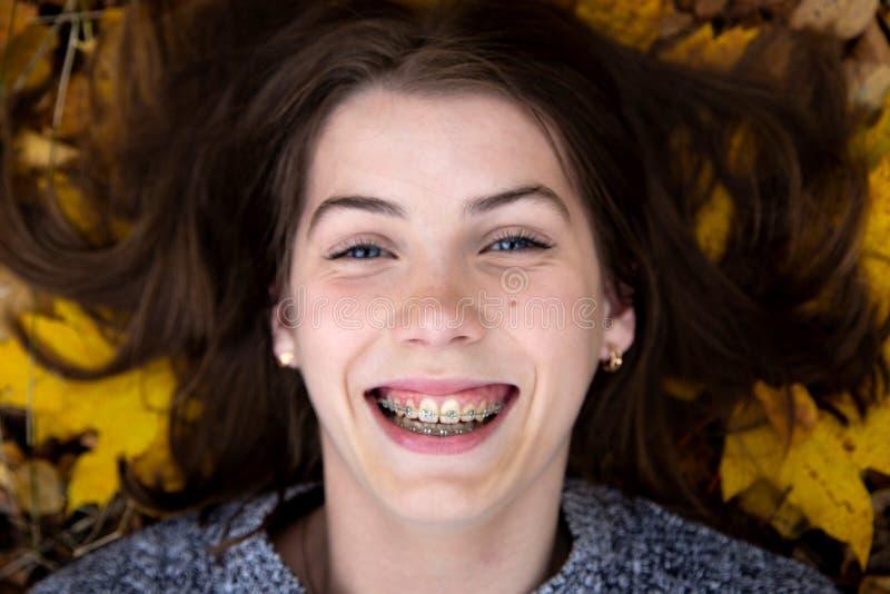 Bästa sikt av en nätt flicka med blåa ögon med ett härligt leende och hänglsen på hennes tänder, som i hösten ligger på jordninge royaltyfria bilder
