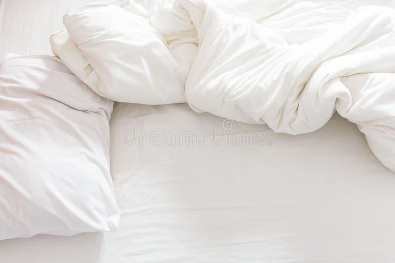 Bästa sikt av en ogjord säng med en kudde, ett sängark och en filt royaltyfri foto