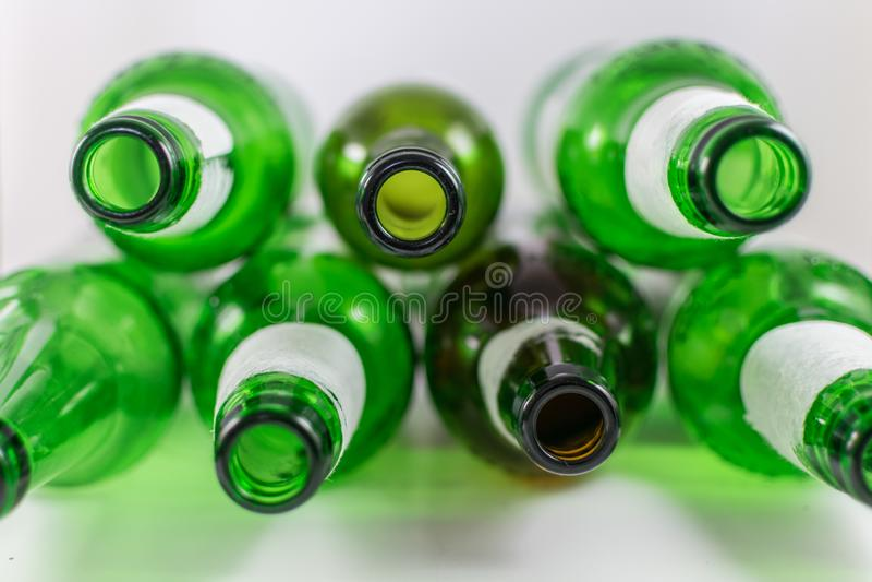Bästa sikt av en packe av tomma gröna och bruna glasflaskor för öl och för vin, med rev sönder etiketter på en vit bakgrund ?tera arkivfoto