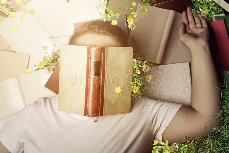bästa sikt av en passionerad avläsare som som sover och lägger på böcker och gräs royaltyfria bilder