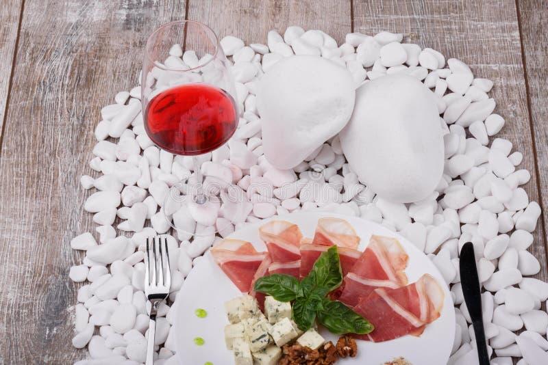 Bästa sikt av en platta med prosciuttoen, roquefortost, valnötter och bazil, ett exponeringsglas av rött vin på en trävit sten arkivfoton
