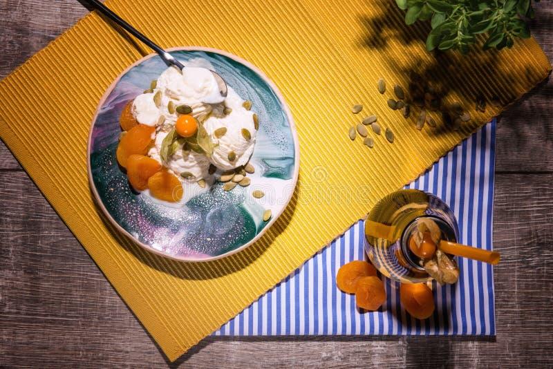 Bästa sikt av en sommarefterrätt Vaniljglass och krus av aprikosfruktsaft på en träbakgrund Krämiga organiska mellanmål royaltyfri foto