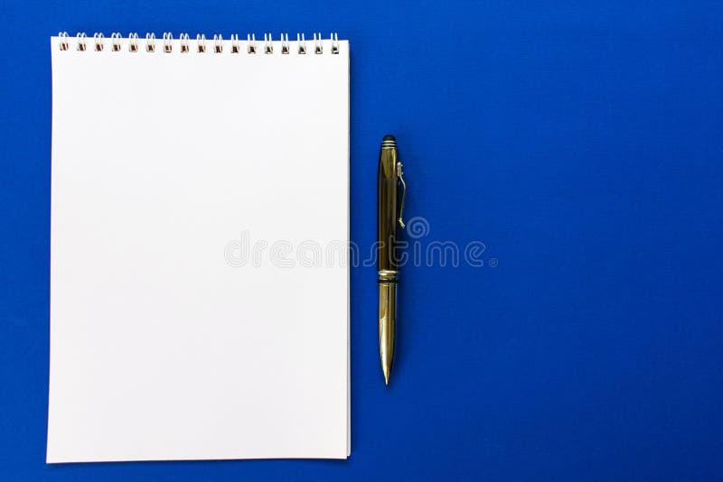 Bästa sikt av en spiral skolaanteckningsbok- och pennsamling på en blå bakgrund för orientering royaltyfri fotografi