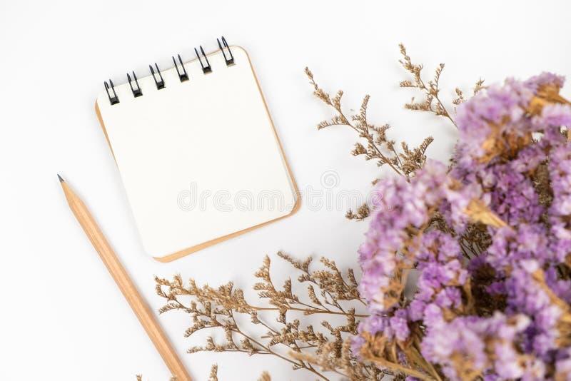 Bästa sikt av en tom pappers- anmärkning med blyertspenna- och blommabuketten royaltyfri fotografi
