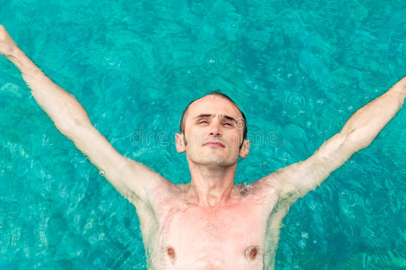 Bästa sikt av en ung man som svävar i simbassäng med öppna armar arkivfoto