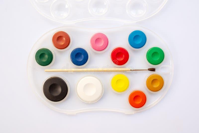 Bästa sikt av en vattenfärgskolapaintbox Måla paletten med borsten tillbaka begreppsskolatillförsel till arkivbilder