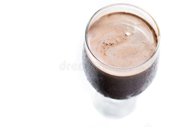 Bästa sikt av ett svettasexponeringsglas av chokladmilkshake i en vit bakgrund arkivbild