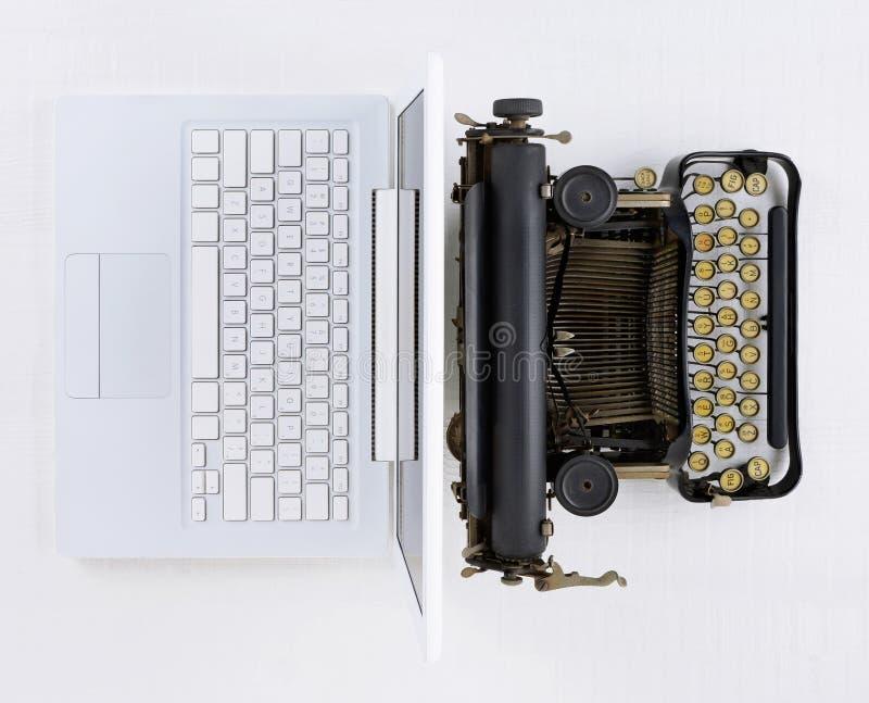 Bästa sikt av ett vitt skrivbord med den gammalmodiga skrivmaskinen som är baksida mot baksida med en bärbar datordator royaltyfria foton