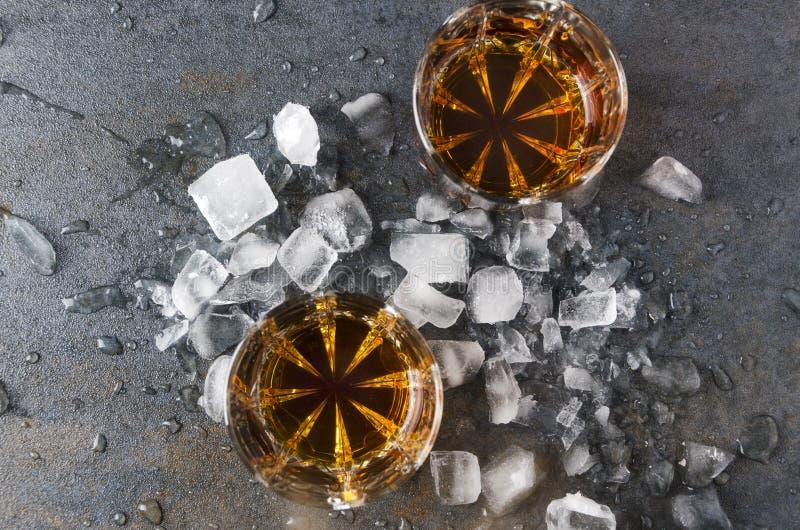 Bästa sikt av exponeringsglas med konjak och stycken av is på grå yttersida cocktail party royaltyfri foto