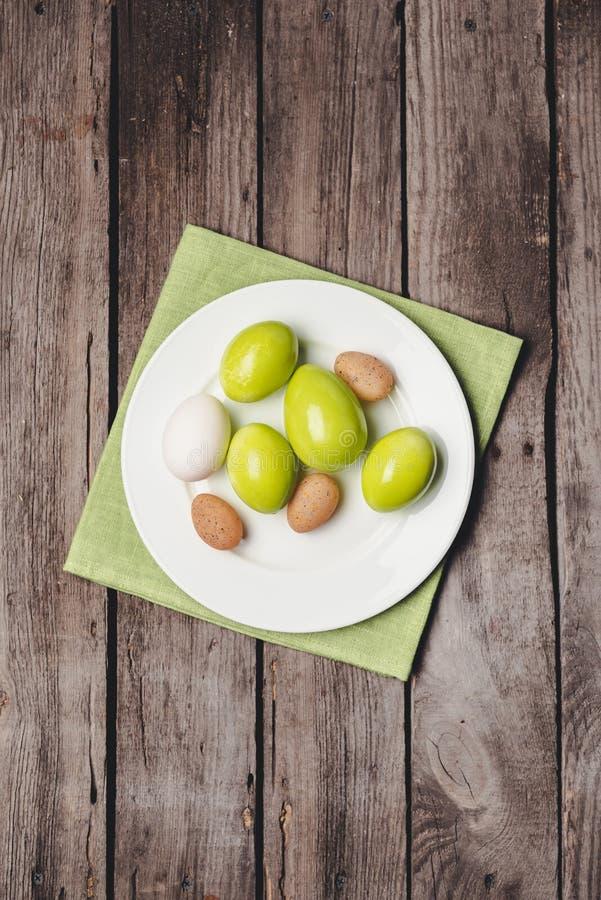 Bästa sikt av färgrika påskägg på den vita plattan och servetten på trätabellen, fotografering för bildbyråer