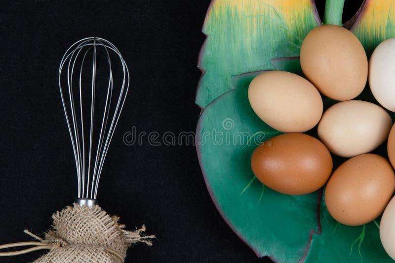 Bästa sikt av fega ägg i en blad formad platta och en eggbeater på en svart bakgrund royaltyfri foto