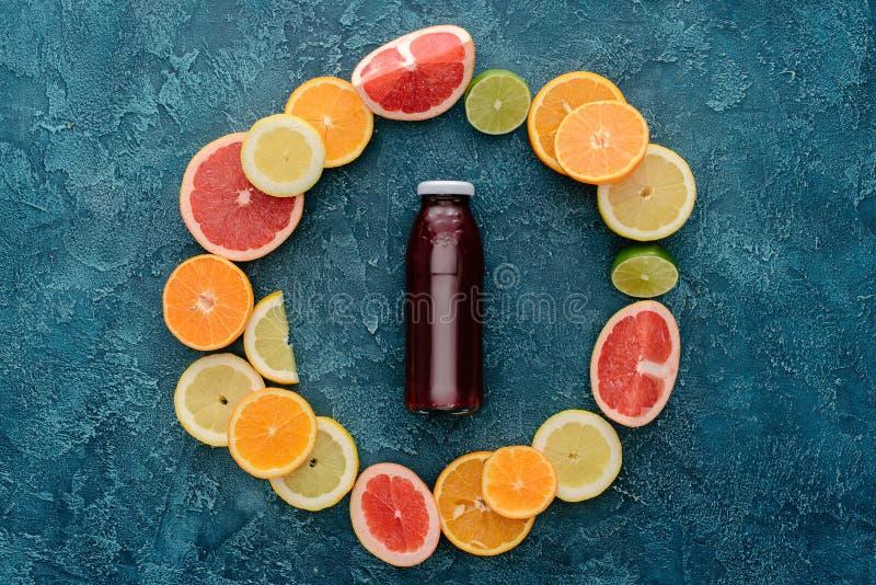 bästa sikt av flaskan av ny fruktsaft som omges med citrusfruktskivor i cirkelform på blått royaltyfri bild