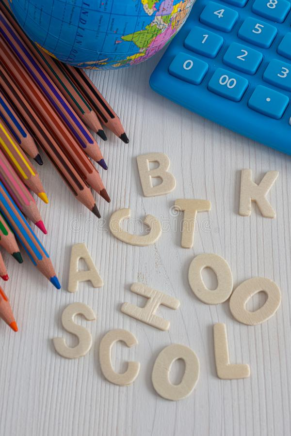 Bästa sikt av flera diagonala kulöra blyertspennor, världsboll och blå räknemaskin, med orden tillbaka till unlinked skola, arkivbilder