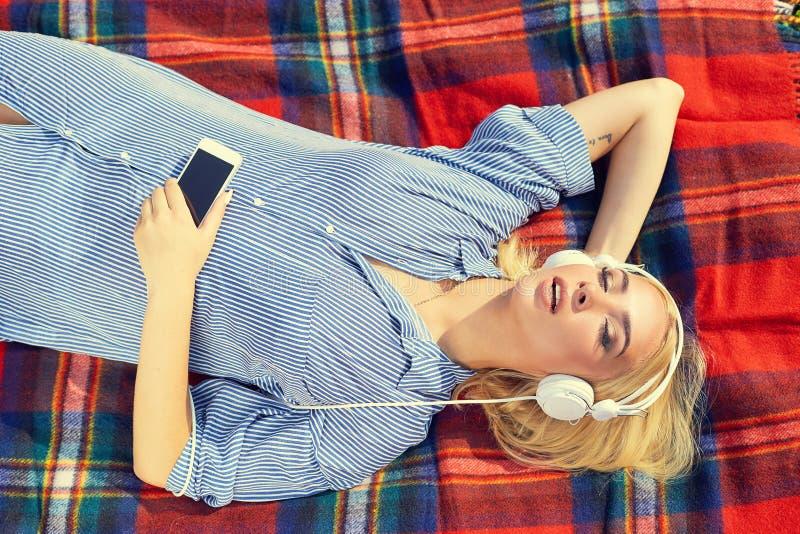 Bästa sikt av flickan som lyssnar till musik som strömmar med hörlurar arkivbilder