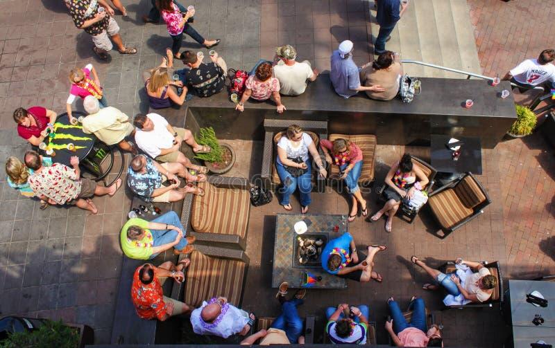 Bästa sikt av folk som omkring sitter med sommarkläder och leis, och drinkar i ett utvändigt sammanträdeområde och på tabeller på arkivbilder