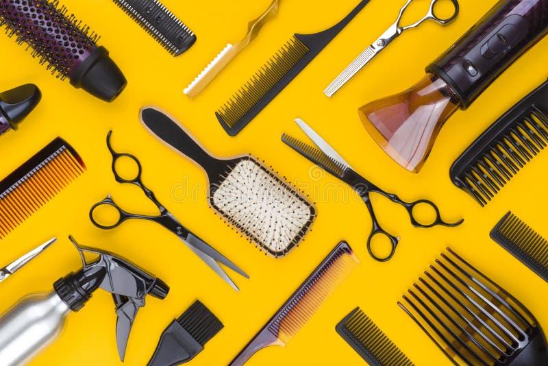 Bästa sikt av frisörhjälpmedel och tillbehör på gul bakgrund fotografering för bildbyråer