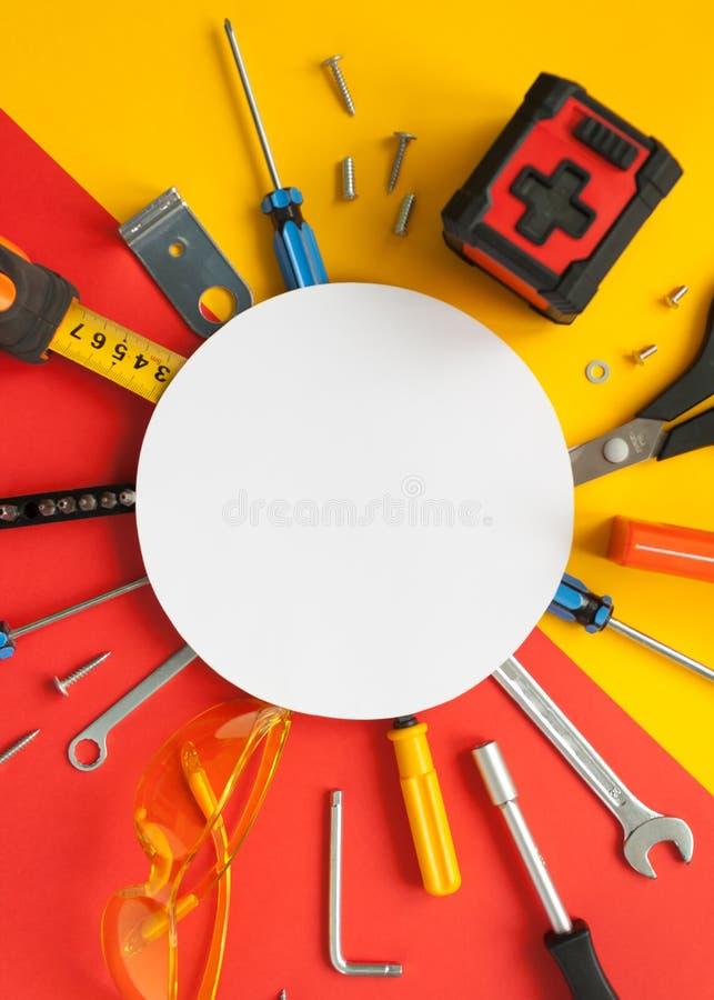 Bästa sikt av funktionsdugliga hjälpmedel, skiftnyckeln, skruvmejseln, nivån, måttbandet, bultar och säkerhetsexponeringsglas arkivbild
