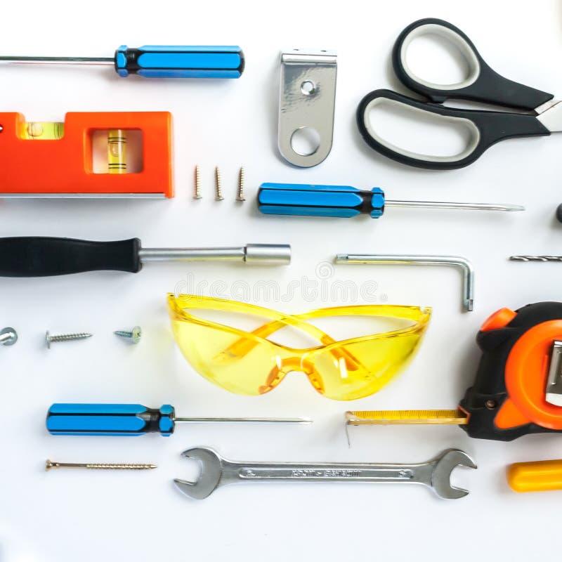 Bästa sikt av funktionsdugliga hjälpmedel, skiftnyckeln, skruvmejseln, nivån, måttbandet, bultar och säkerhetsexponeringsglas på  arkivbilder