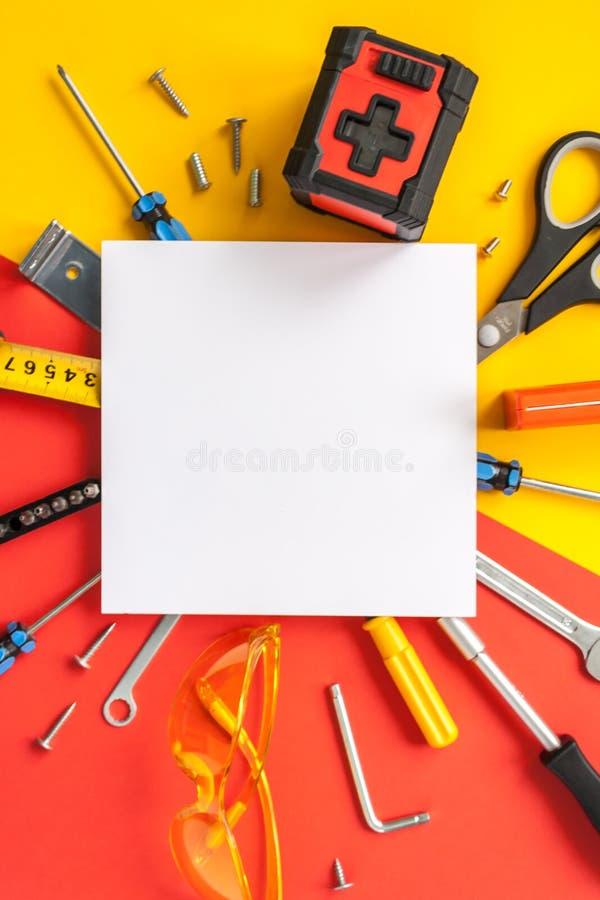 Bästa sikt av funktionsdugliga hjälpmedel, skiftnyckeln, skruvmejseln, nivån, måttbandet, bultar och säkerhetsexponeringsglas på  arkivfoto