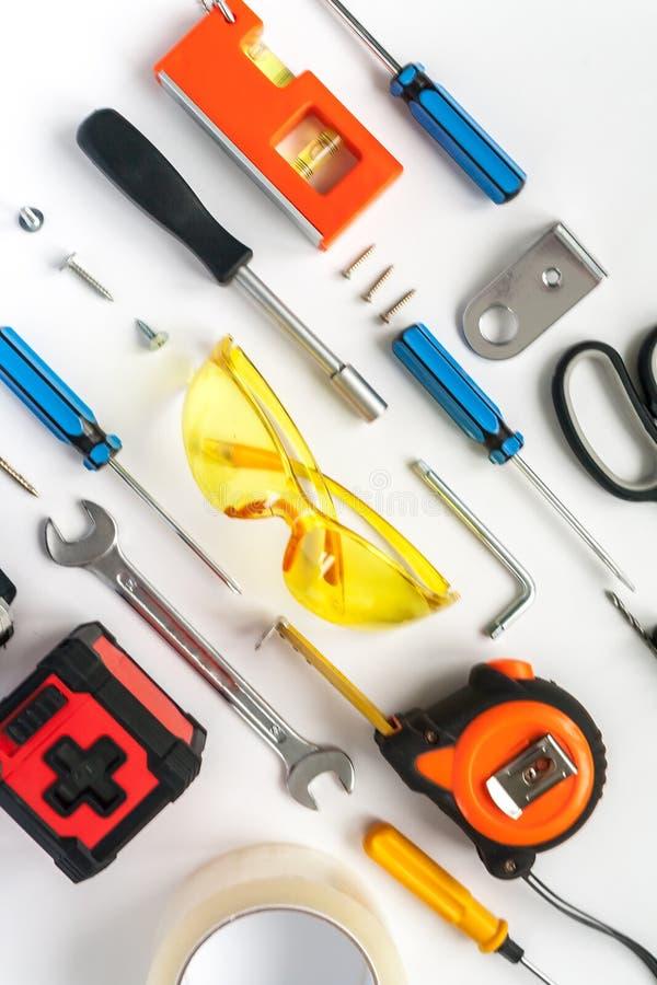 Bästa sikt av funktionsdugliga hjälpmedel, skiftnyckeln, skruvmejseln, nivån, måttbandet, bultar och säkerhetsexponeringsglas på  arkivbild